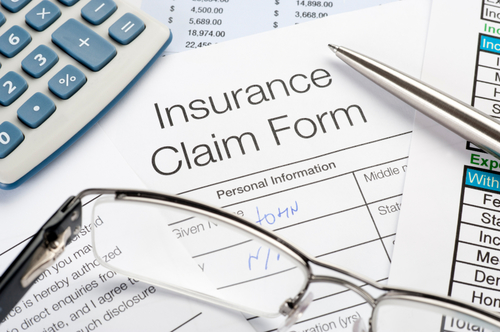 Handwritten Insurance Claim Form with pen and calculator